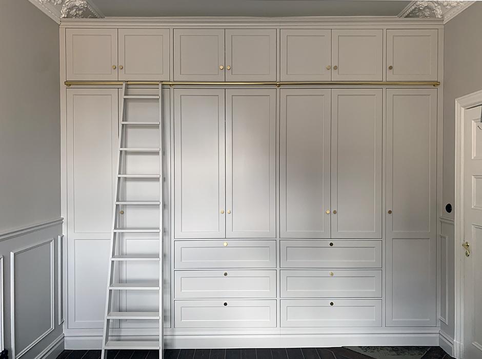 Platsbyggd garderob med stege.